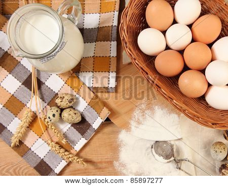 Eggs and wheat on wooden table