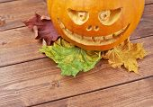 image of jack o lanterns  - Scary jack o lantern pumpkin composition next to colorful maple leaves over the wooden boards surface
