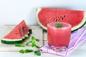 stock photo of mints  - Glass of fresh watermelon juice with mint leaves and sliced fruit on wooden table - JPG