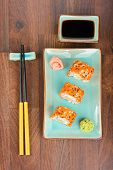 stock photo of masago  - Sushi rolls with masago served on turquoise plate with pickled ginger soy sauce and chopsticks on wooden table - JPG