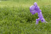 picture of animal teeth  - Purple balloon animal dinosaur with teeth and eyes looking scary in the lush green grass of a back yard