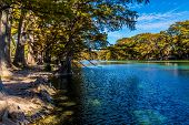 stock photo of crystal clear  - Rocky River Bed of the Crystal Clear Frio River.  Fall foliage on Bald Cypress Trees.