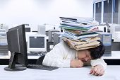 stock photo of overwhelming  - Portrait of overwhelmed fat man sleeping in office with documents on his head - JPG