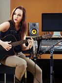 picture of recording studio  - Photo of a beautiful brunette in a recording studio recording her guitar tracks - JPG