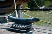 pic of dock  - Large black metal cleat on a wooden dock with a large white rope or line wrapped around in securing a wooden boat visible in background   - JPG