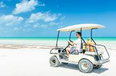 picture of caribbean  - Cute young man driving golf cart along tropical white sandy beach during his Caribbean vacation on Holbox island Mexico - JPG