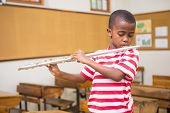 picture of pupils  - Cute pupil playing flute in classroom at the elementary school - JPG
