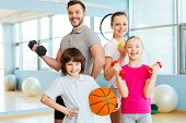 stock photo of clubbing  - Happy family holding different sports equipment while standing close to each other in health club - JPG