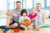 stock photo of physical education  - Happy sporty family bonding to each other while sitting on exercise mat together - JPG