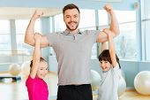picture of physical education  - Cheerful young sporty father showing his biceps while children bonding to him and smiling - JPG