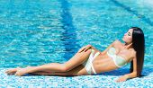 stock photo of sunburn  - Beautiful woman relaxing in a pool at summer - JPG