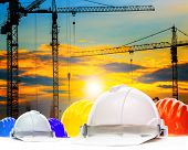 picture of structural engineering  - safety helmet and structure of high crane in construction site against beautiful evening sky use for engineering and architecture - JPG