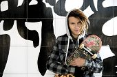 picture of rasta  - portrait of young guy with skateboard and rasta hair in a lifestyle concept - JPG
