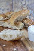 stock photo of flat-bread  - flat bread sticks with Tzatziki garlic dip on a rustic wooden table - JPG