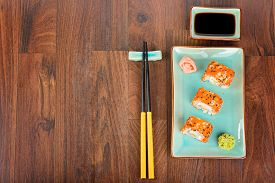 image of soy sauce  - Sushi rolls with masago served on turquoise plate with pickled ginger soy sauce and chopsticks on wooden table - JPG