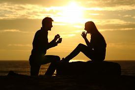 stock photo of married  - Proposal on the beach with a man silhouette asking for marry at sunset with the sun in the background - JPG