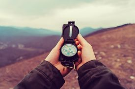 stock photo of pov  - Hiker woman searching direction with a compass in the mountains - JPG