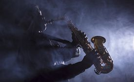 foto of saxophone player  - African American jazz musician playing the saxophone through smokey light in club - JPG