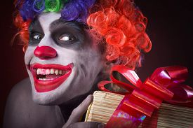 stock photo of clowns  - scary clown makeup and with a terrible gift in hand in the hands - JPG