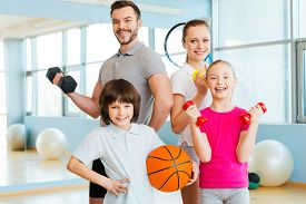 image of physical education  - Happy family holding different sports equipment while standing close to each other in health club - JPG