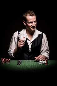 foto of gambler  - A male gambler smiling leaves four aces and winning hand - JPG