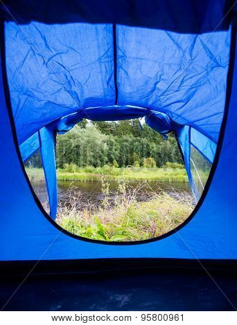 camping, travel, tourism, hike and people concept - view from blue tourist tent entrance to lake or river landscape