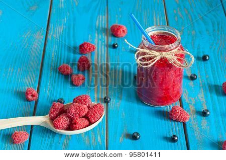 Mason jar with raspberry jam or marmalade and fresh raspberries, blueberries on a rustic wooden tabl