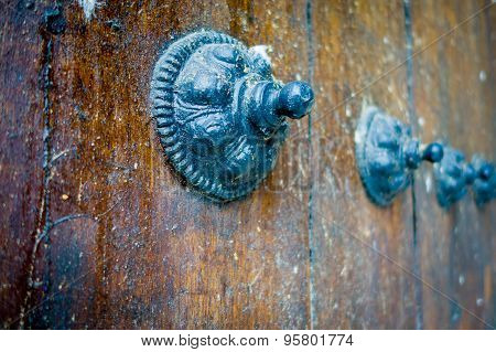 Closeup of an old wooden door with timeless designed black metal knobs as decorations