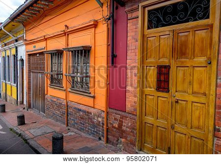 Wooden entrance door next to barred windows and colorful walls on streetlevel typical for small town