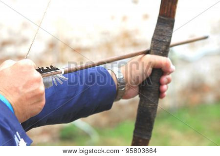 Businessman holding bow and shooting to archery target