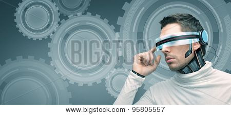 people, technology, future, engineering and progress - man with futuristic 3d glasses and microchip implant or sensors over blue background with cogwheel mechanism projection