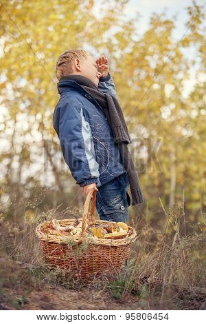 Boy With Full Basket Of Mushrooms In Forest