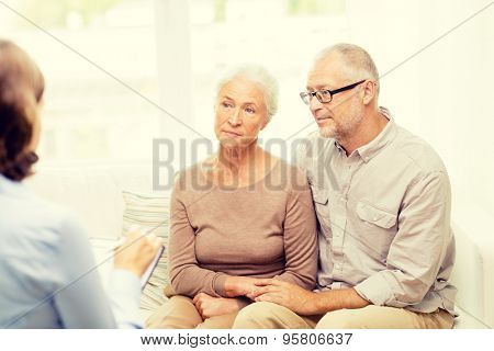 family, relations, age and people concept - senior couple and psychologist or social worker at home