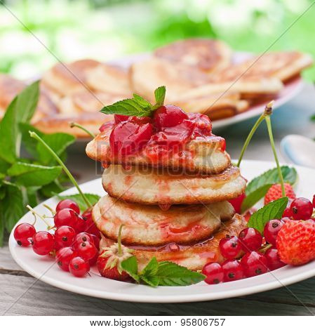 Pancakes with berries on a wooden background in a summer garden