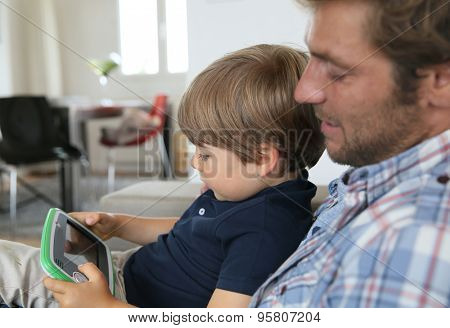 Daddy with son playing with video game player