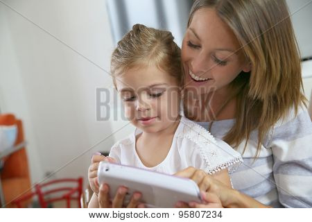 Mommy with little girl playing with video game player
