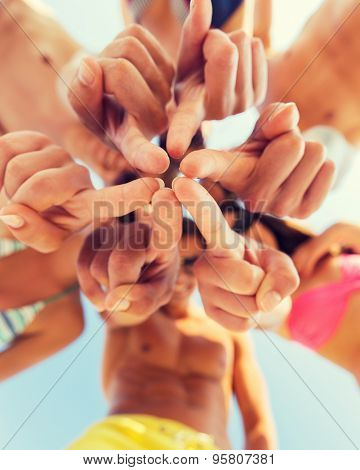 friendship, happiness, summer vacation, holidays and people concept - close up of smiling friends wearing swimwear standing in circle over blue sky