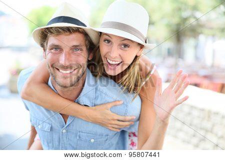 Cheerful man giving piggyback ride to girlfriend