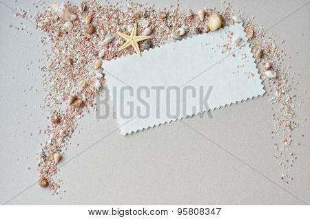 Sea shells, pink sand and invitation card on a paper background