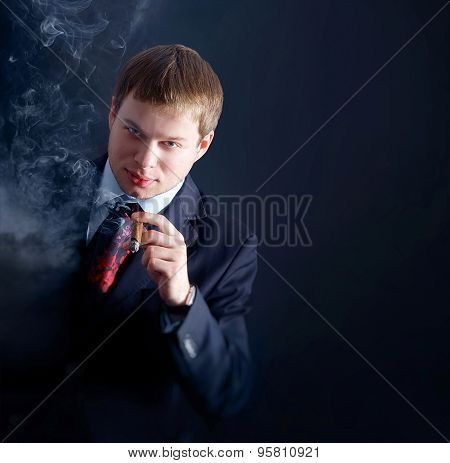 The man in suit smoke a cigar, looks at us. lots of smoke. A dark background