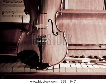 Violin And Bow On Piano With Sheet Music