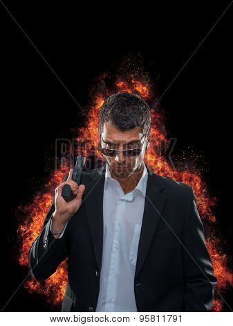 Man in suit with a gun on explosion background