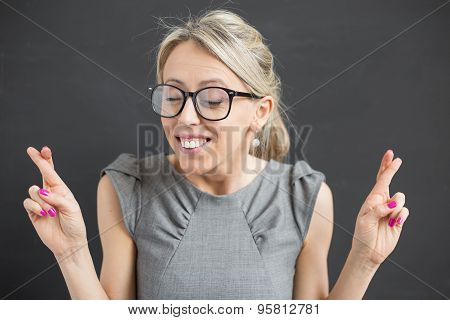 Young cheerful woman with fingers crossed