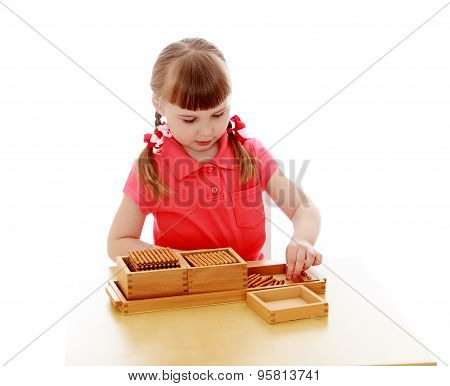 Adorable little blonde girl sitting at table and studying math in a Montessori kindergarten, close-u