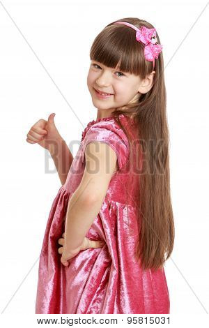 Beautiful girl with long, lush hair and short bangs in pink velvet