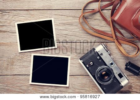 Vintage film camera and two blank photo frames on wooden table. Top view