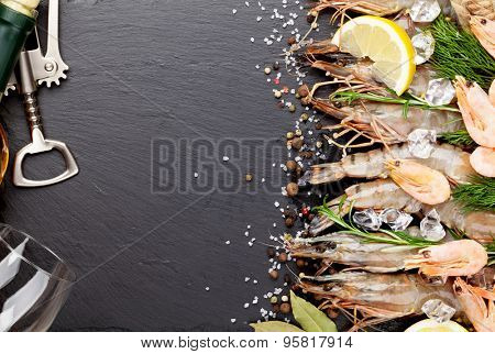 Fresh prawns with spices and white wine on black stone background. Top view with copy space