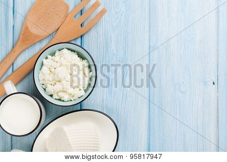 Dairy products on wooden table. Milk, cheese, curd cheese and butter. Top view with copy space