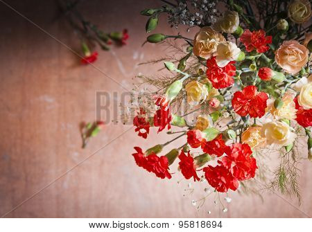Carnations And Gypsophelia Against Wooden Background