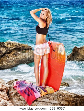 Pretty woman spending active summer holidays on the rocky coast, standing back side and looks over her shoulder, holding surfboard and preparing to swim